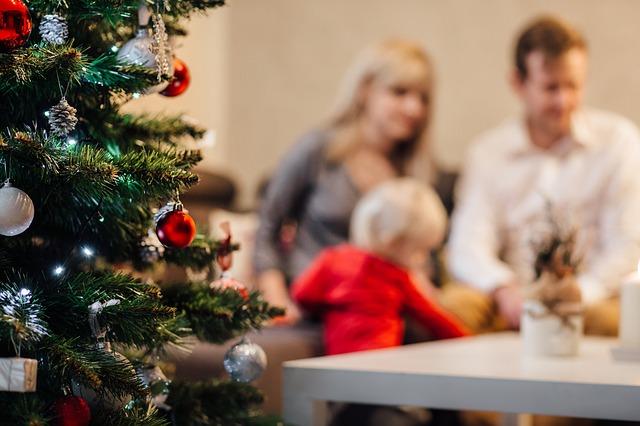 Etualalla joulukuusi ja taka-alalla perhe pöydän ääressä